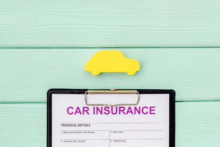 Buying new auto concept with insurance form and car toy on mint green wooden background top view copy space