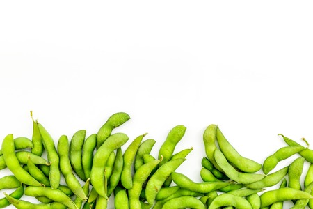 Vegan food concept with green soybeans or edamame on white desk background top view