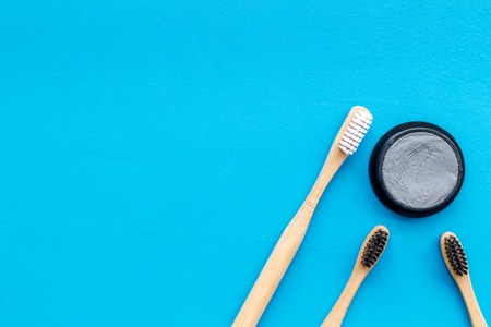 Zero waste lifestyle concept. Dental care with eco friendly bamboo tooth brush and carbon toothpaste on blue background top view space for text Stock Photo