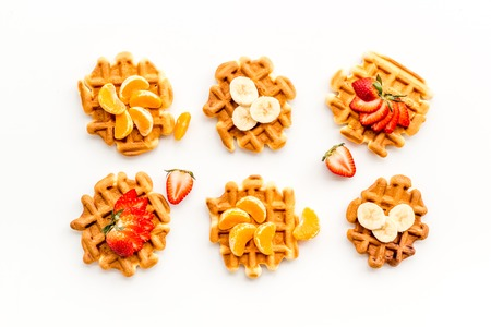 Sweet snack. Viennese waffles. Homemade Belgian waffles with fruit toppings on white background top view