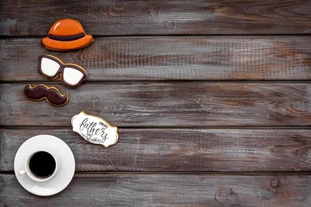 帽子,小胡子,眼镜。设计为父亲节庆祝党用曲奇饼,礼物盒和咖啡在木背景顶视图嘲笑