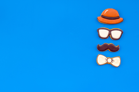 Happy Father Day celebration with cookies in shape of bow tie, moustache, glasses and hat on blue background top view mockup