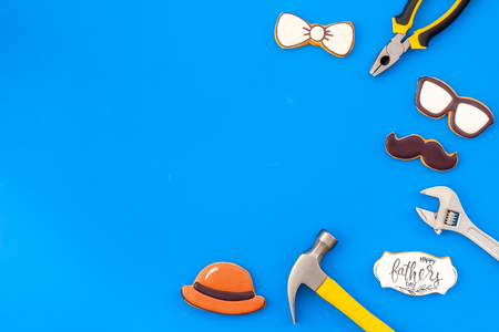 Happy Father Day celebration with cookies in shape of bow tie, moustache, glasses and hat and instruments on blue background top view mockup