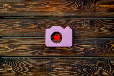 Concepto de cámara de fotos con corazón en la vista superior de fondo de madera. Foto de archivo