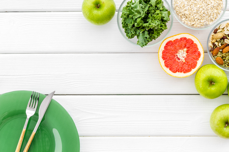 Proper nutrition. Weight loss concept with green organic food on white wooden background top view space for text
