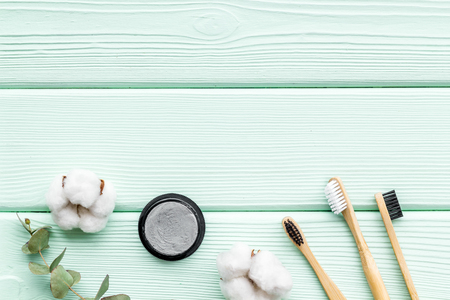 Zero waste lifestyle concept. Dental care with eco friendly bamboo tooth brush and carbon toothpaste on mint green wooden background top view space for text