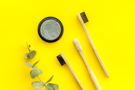 Dental care. Eco materials concept with bamboo tooth brush, toothpaste with bamboo carbon and plant on yellow background top view Stock Photo