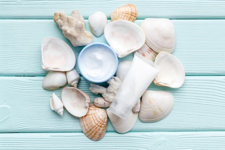 Skin care concept. Cosmetics with Dead Sea minerals. Cream, lotion and shells on mint green wooden table background top view Archivio Fotografico - 121973507