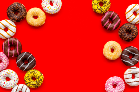 Sweet break concept. Traditional american donuts of different flavors frame on red background flat lay mockup 免版税图像