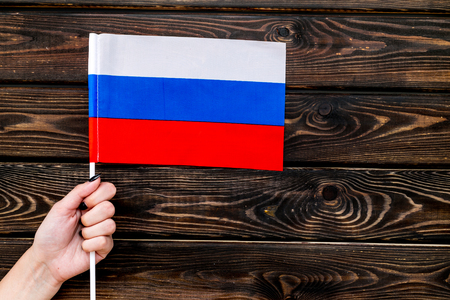 Flag of Russia in hand on wooden background top view.
