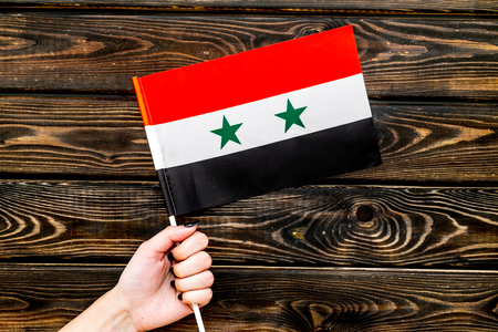 Flag of Syria in hand on wooden background top view.
