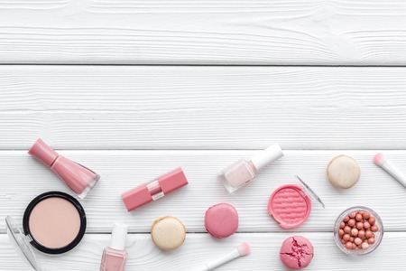 Blusher, powder, lipstick, nail polish. Make-up accessories, fashion stylish cosmetics and macaroon on white wooden desk background top view copy space