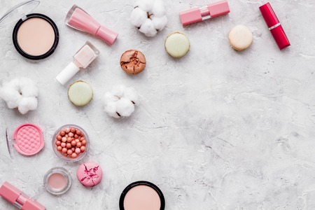 Blusher, powder, lipstick, nail polish. Make-up accessories, fashion stylish cosmetics and macaroon on stone desk background top view copy space 免版税图像