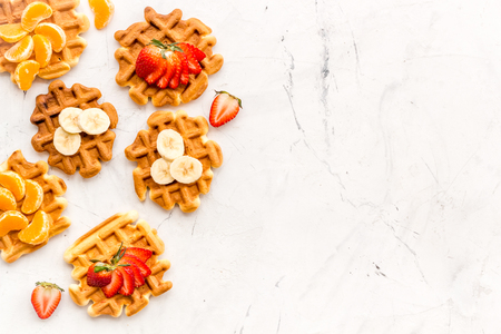 Sweet snack. Viennese waffles. Homemade Belgian waffles with fruit toppings on white marble background top view space for text