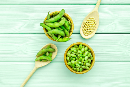 Ingredients. Green soybeans or edamame in spoon and bowl for fresh healthy organic food on mint green wooden background top view