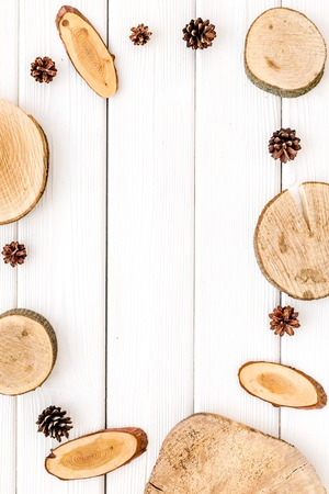 Wooden sawcut and pine cone frame for blog title on white wooden background top view mockup