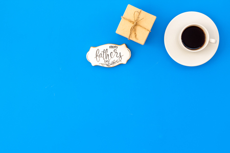 Happy Father Day celebration with gift and cup of coffee on blue background top view mockup