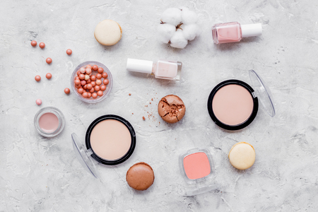 Blusher, powder, nail polish. Decorative cosmetics for make-up with macaroon cookies on gray stone tabletop background