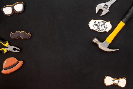 Happy Father Day celebration with cookies in shape of bow tie, moustache, glasses and hat and instruments on black background top view mockup