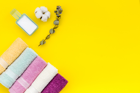 Products of cotton set. Preparing for laundry with washing powder and towels on yellow background top view copy space