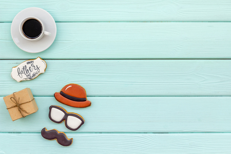 Hat, moustache, glasses figures. Design for Father Day celebration party with cookies, gift box and coffee on mint green wooden background top view mock up