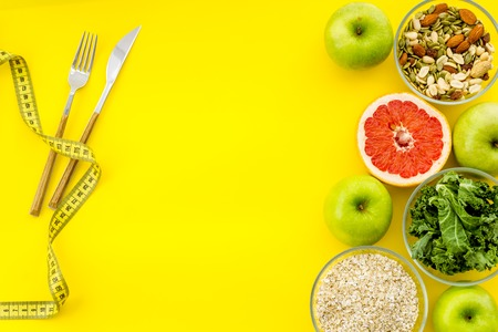 Proper nutrition. Weight loss concept with green organic food on yellow background top view space for text