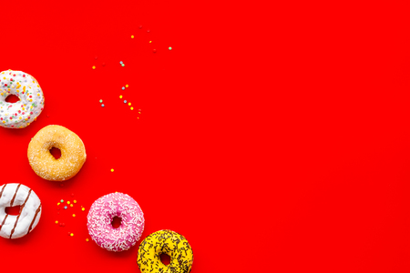 Homemade bakery. Donuts of different flavors for breakfast on red background top view space for text