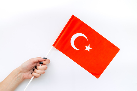 Flag of Turkey in hand on white background top view.