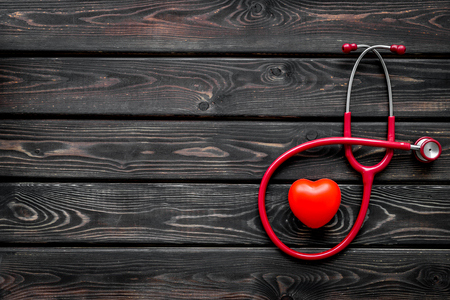 Hospital and diagnostic concept. Stethoscope and heart for family doctor set to cure of cardiac disease on wooden background top view space for text
