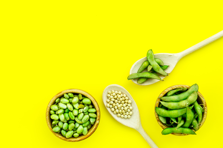 Ingredients. Green soybeans or edamame in spoon and bowl for fresh healthy organic food on yellow background top view space for text
