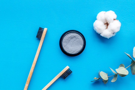 Zero waste lifestyle concept. Dental care with eco friendly bamboo tooth brush and carbon toothpaste on blue background top view
