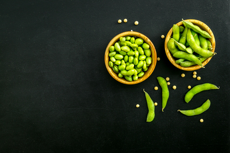 Vegan food concept with green soybeans or edamame on black desk background top view copy space