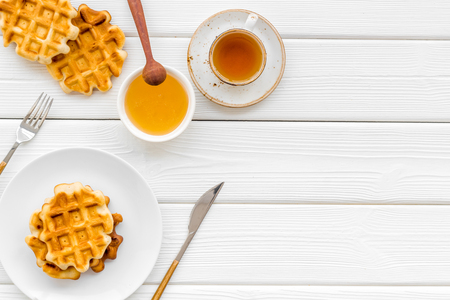 Sweet breakfast. Homemade Viennese waffles with honey and tea, flatware on white wooden background top view space for text