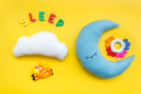 Baby care concept. Sleep copy for baby pattern with moon pillow, cloud, toy on yellow background top view