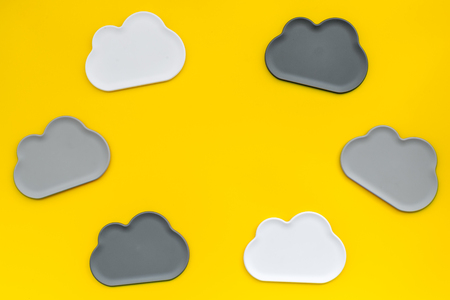 Cloud computing concept with clouds on yellow work desk background top view space for text Фото со стока
