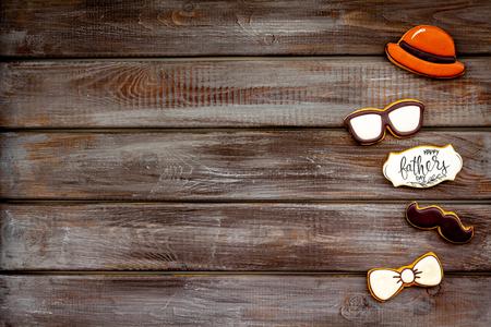 帽子,小胡子,眼镜,蝴蝶结系列。设计为父亲节庆祝党用在木背景顶视图样机的曲奇饼