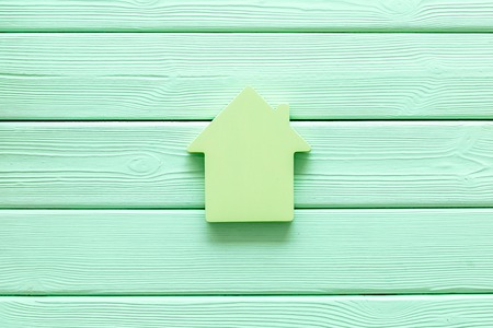 Property insurance concept. Buy house with house figure on office desk mint green wooden background top view