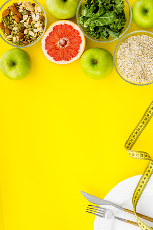 Fitness diet. Weight loss concept with oatmeal, nuts, greenery, fruits and measuring tape on yellow background top view copy space Фото со стока