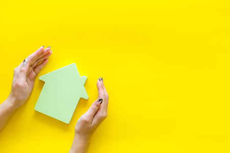 New house purchase. Property insurance concept with house toy in hands on yellow background top view Stock Photo