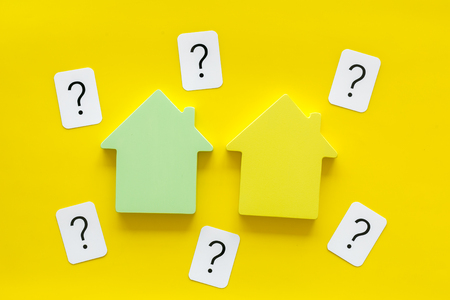 Property insurance concept. Buy house with house figure and question mark on office desk yellow background top view