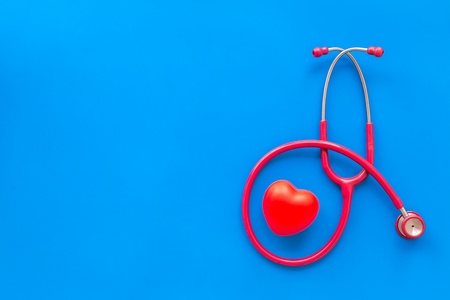 Family doctor. Cardiologist. Diagnostic and cure of cardiac disease with stethoscope and heart on blue background top view mock-up
