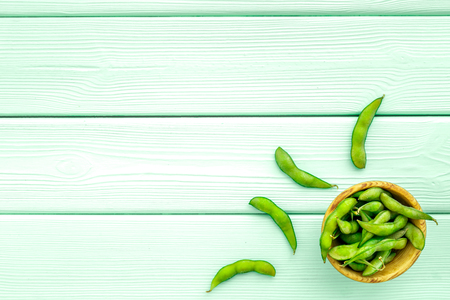 Healthy food. Edamame in bowls on mint green wooden background top view mock up