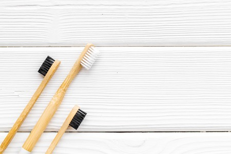 Zero waste lifestyle concept. Dental care with eco friendly bamboo tooth brush on white wooden background top view space for text