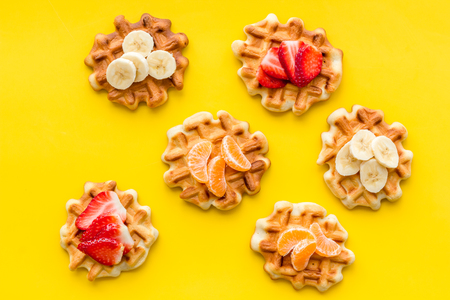 Sweet snack. Viennese waffles. Homemade Belgian waffles with fruit toppings on yellow background top view Stock fotó