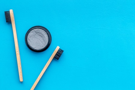 Zero waste lifestyle concept. Dental care with eco friendly bamboo tooth brush and carbon toothpaste on blue background top view space for text Banco de Imagens