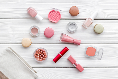 Blusher, lipstick, bag, nail polish. Make-up accessories, fashion stylish cosmetics and macaroon on white wooden desk background top view pattern