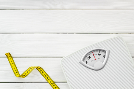 Diet. Bathroom scales and measuring tape for weight loss concept on white wooden background top view copy space