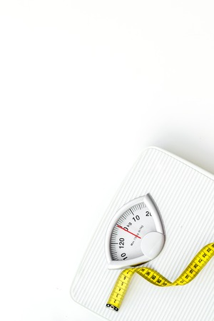 Diet. Bathroom scales and measuring tape for weight loss concept on white background top view space for text