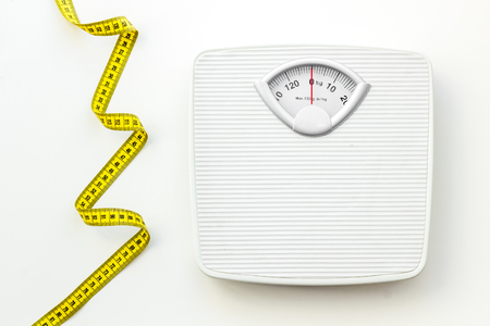 Diet. Bathroom scales and measuring tape for weight loss concept on white background top view Banco de Imagens