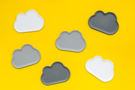 Share information on the Internet. Clouds figures for cloud storage on yellow office background top view